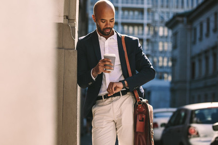 Businessman checking time outdoors
