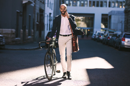 Businessman going to office with bicycle using phone