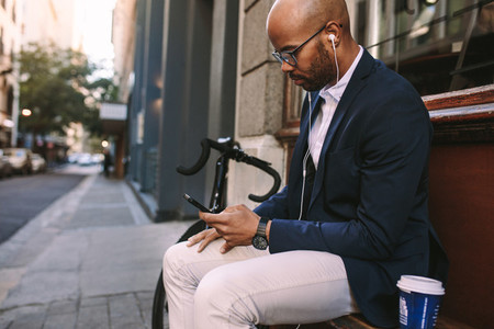Businessman relaxing outdoors using phone