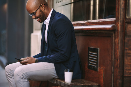 Businessman using smart phone sitting outside