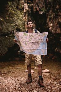 Hiker using a map to find the route to the destination