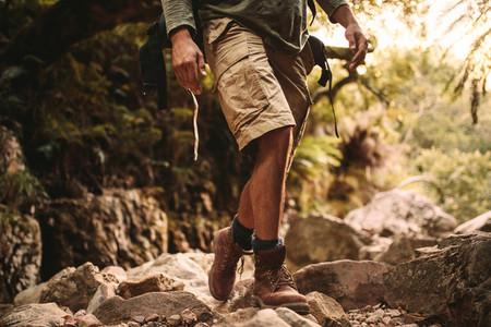 Man in trekking gear hiking on rocky trail