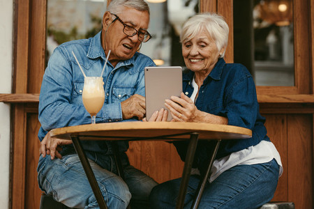 Old couple using tablet pc at cafe