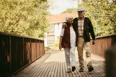 Happy elderly couple walking through a park