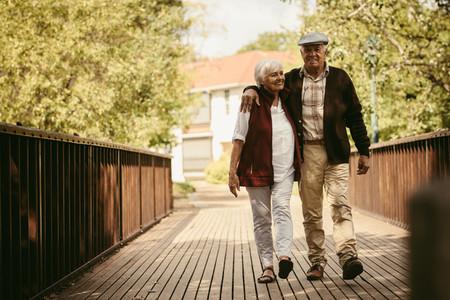 Happy elderly couple walking through a park