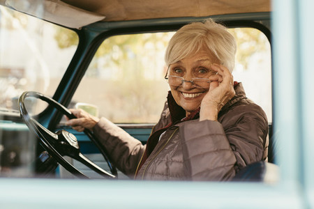 Elder woman driving a old car