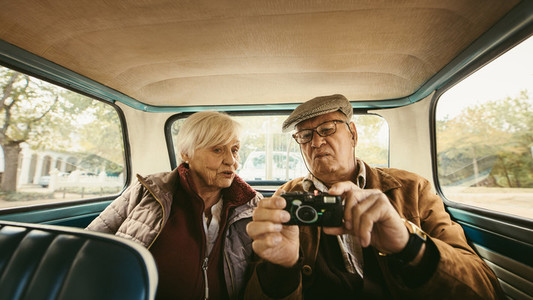 Old couple in car looking at the pictures on camera