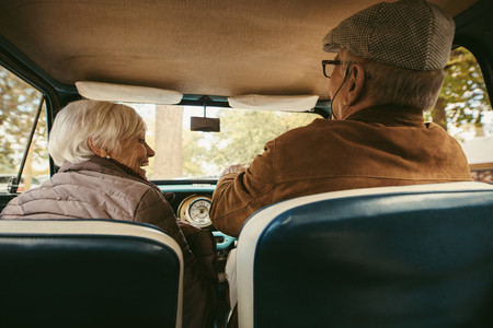 Old couple driving a car on a winter day