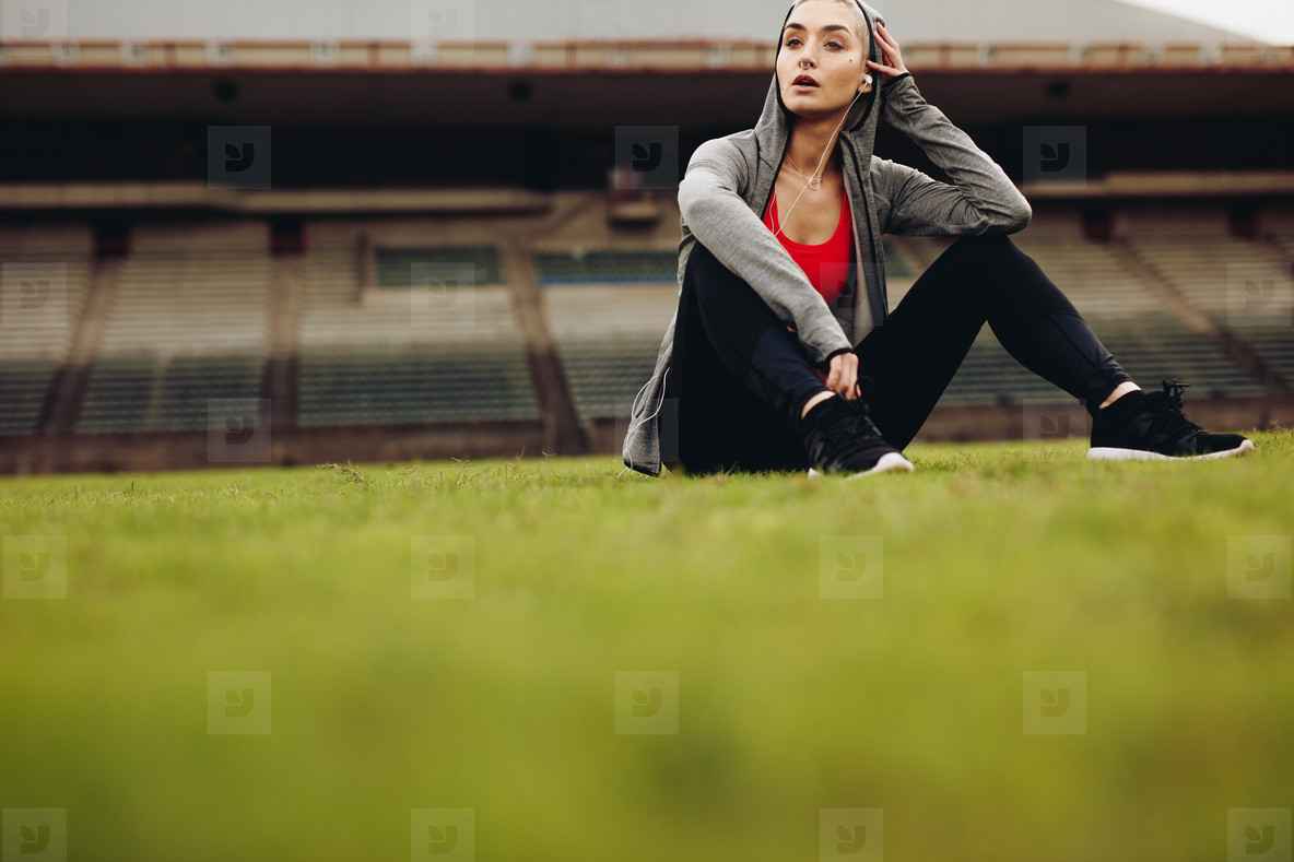Woman relaxing after workout sitting on grass in stadium