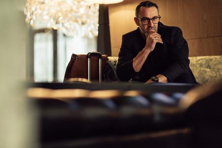 Businessman waiting at hotel lobby looking at camera