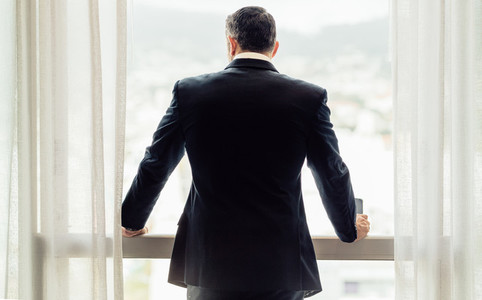 Businessman standing by hotel room window