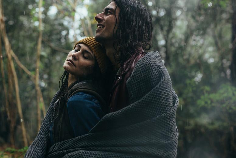 Romantic couple standing under the rain