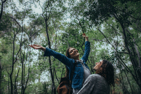 Woman enjoying the fresh climate in forest with boyfriend