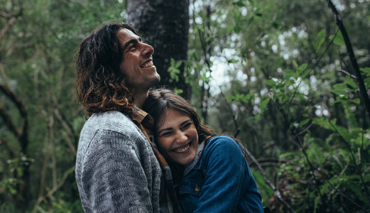 Couple having great time in forest during rain