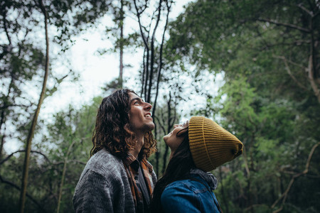 Loving couple looking up and smiling in forest
