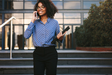 Businesswoman walking outside talking over phone