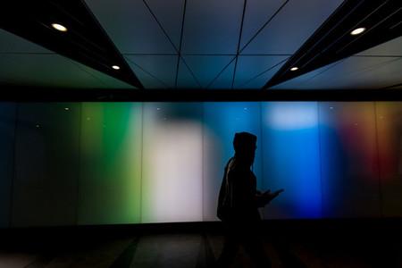 Young man walking using phone in futuristic modern sci fi moody