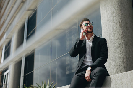Businessman talking over mobile phone sitting outdoors