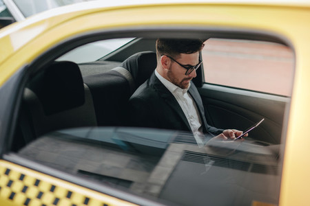 Businessman sitting in cab using his mobile phone