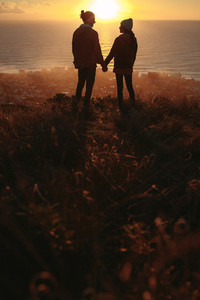 Loving couple on mountain peak during sunset