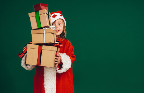 Kid in santa costume holding gift boxes