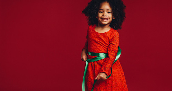 Little girl playing with a satin ribbon