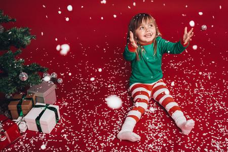 Kid sitting beside a christmas tree enjoying artificial snowfall