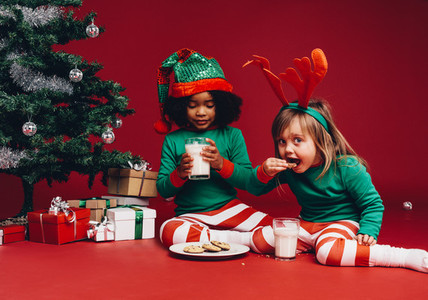 Little girls eating cookies sitting beside a christmas tree