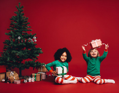 Children playing with christmas gift boxes