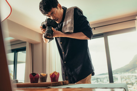 Food photographer taking pictures of cupcakes