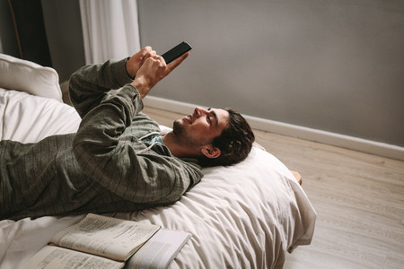 Man looking at mobile phone lying on bed