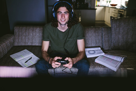 Student playing video game sitting on couch at home