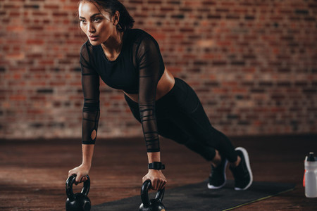 Strong woman doing push ups on kettle bell