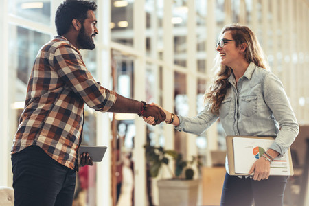 Happy business partners greeting each other at a meeting