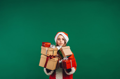 Girl in santa claus costume holding gift boxes