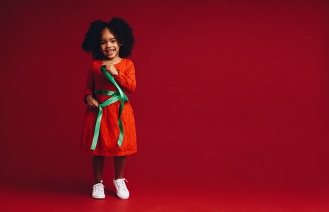 Smiling kid playing with a satin ribbon around her waist