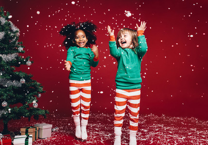 Little girls playing with artificial snow flakes