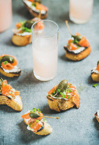 Crostini with smoked salmon and grapefruit cocktails selective focus