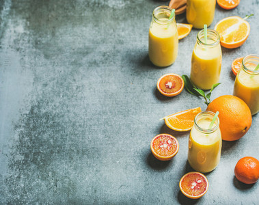Healthy yellow smoothie in bottles over concrete background  copy space