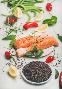 Raw salmon steaks with vegetables  greens and rice  marble background