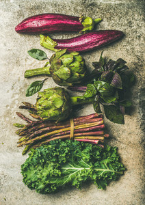 Flat lay of fresh green and purple vegetables vertical composition