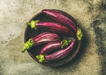 Flat lay of fresh raw Fall harvest purple eggplants in bowl