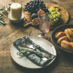 Plate with linen napkin fork spoon glass candle fruits bread