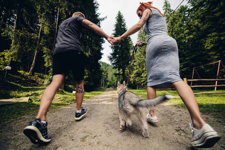couple runs on road in the nature with dog