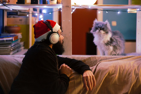 Young man with headphones and christmas hat looking at his cat on a sofa