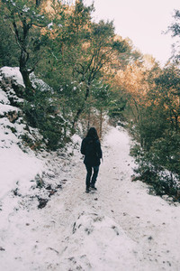 Girl walking on her back on a snowy mountain trail