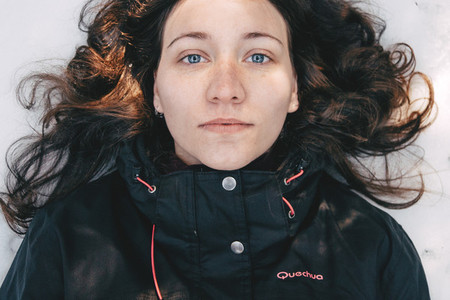 Blue eyed girl lying on top of snow looking at camera