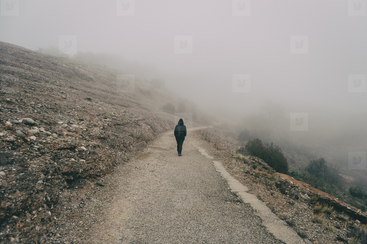Girl walking on a mountain road with a lot of fog