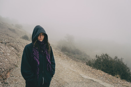 Girl with hood in a mountain landscape with a lot of fog