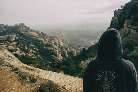 Girl on her back with a hood looking at a landscape of mountains